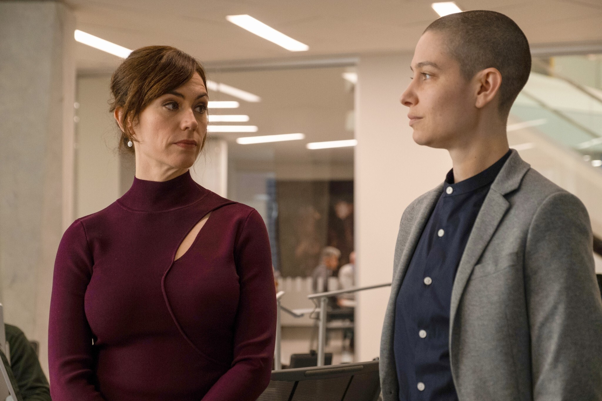 Maggie Siff and Asia Kate Dillon look at each other in an office