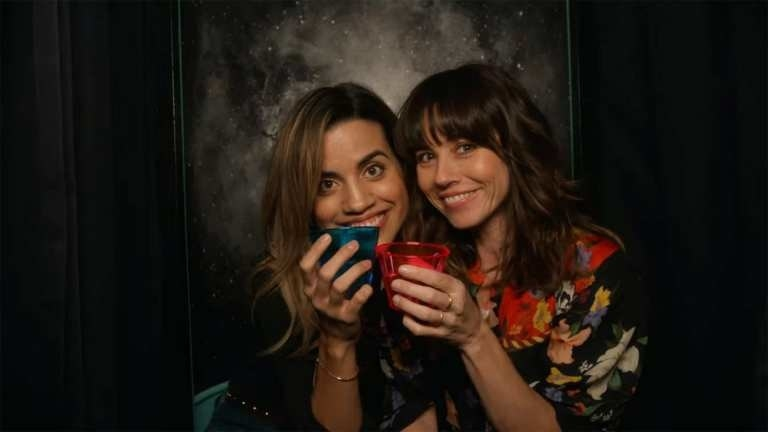 Natalie Morales and Linda Cardellini cheers in a photo booth