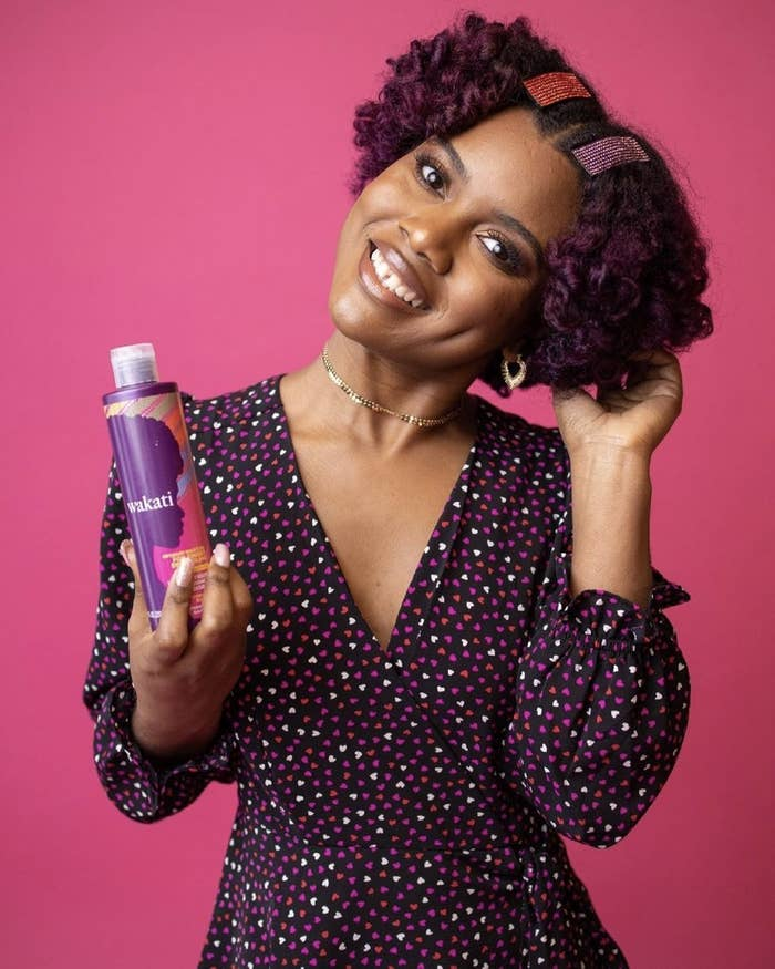 A woman holding a bottle of detangling conditioner