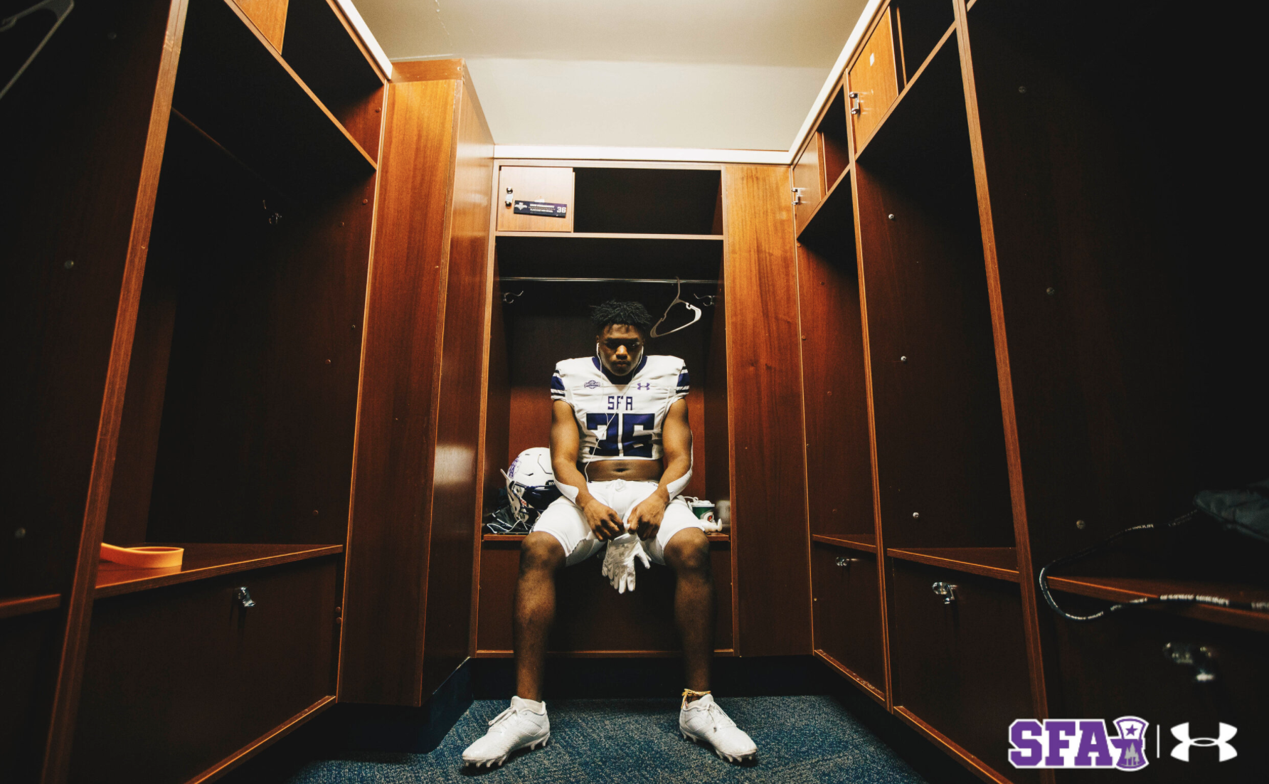 A football player sits alone in an empty locker room