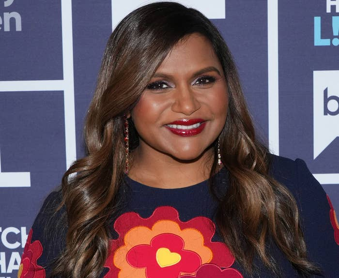 Mindy smiles while wearing a blue dress with orange and red flowers