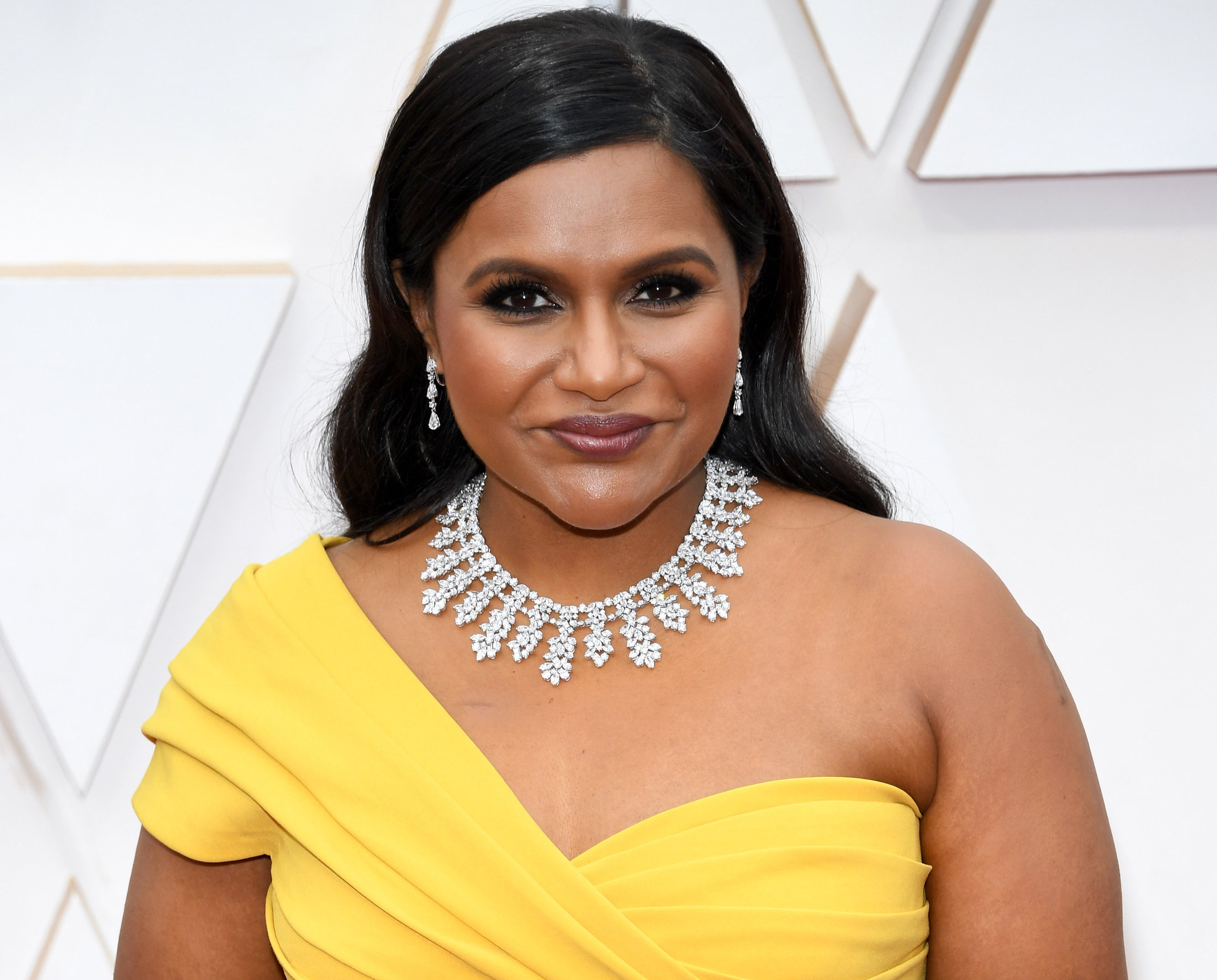 Mindy wears a yellow one-shoulder dress with a diamond necklace