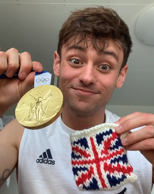 Tom smiling while holding up his Olympic gold medal and his knitted cosy