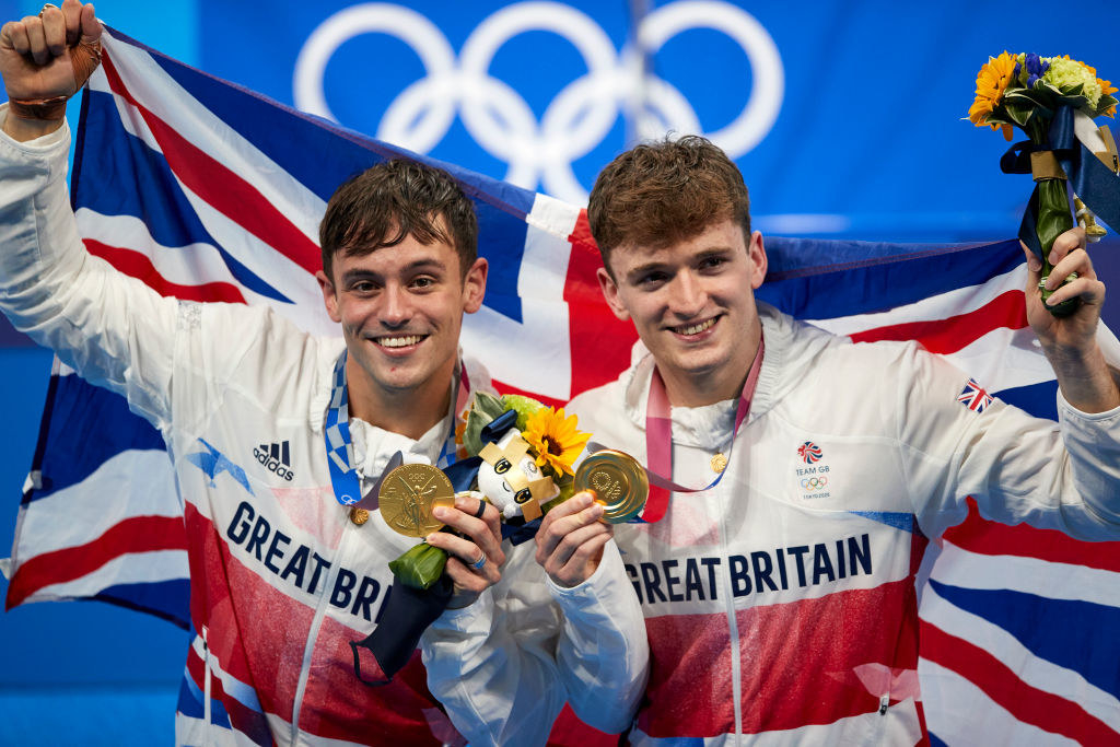 Tom Daley and his teammate Matty Lee holding up their Olympic gold medals and smiling