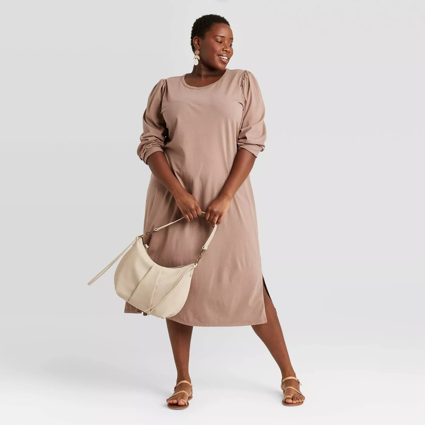 Model wearing light brown dress with puff sleeves, two slits on each side, goes past the knee