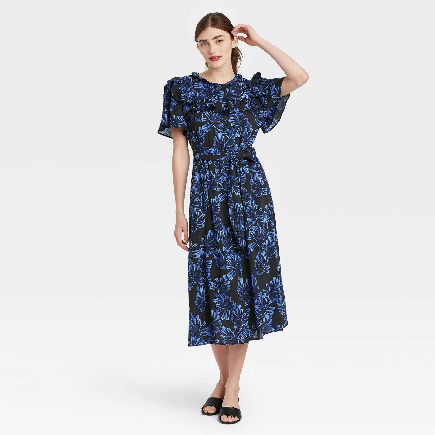 Model wearing midi dress with black and blue leaf pattern, goes past the knee