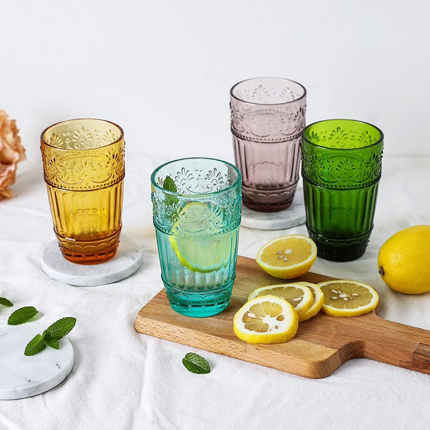 Four glasses in different colors, each printed with embossed moulding design and rivets for an easy grip