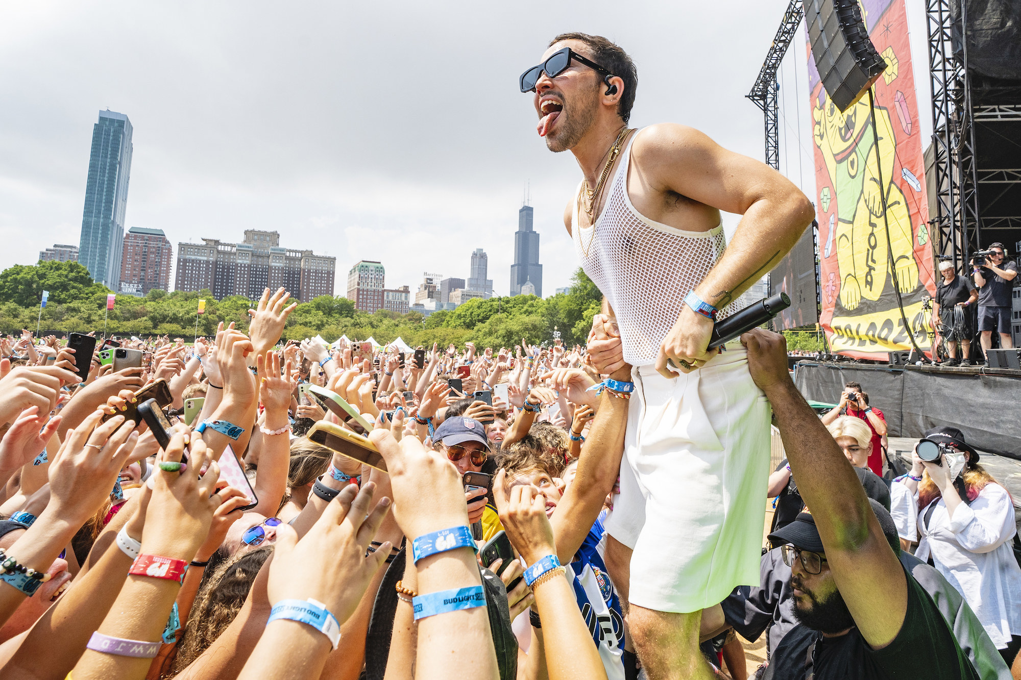 Musician Max Schneider stands above a crowd of young people as he performs at Lollapalooza music festival in Chicago.