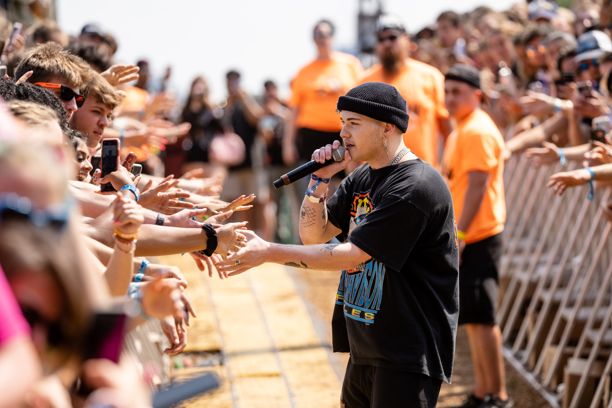 Musician Trevor Daniel shakes hands and sings as he moves through the crowd along the barricades at Lollapalooza.