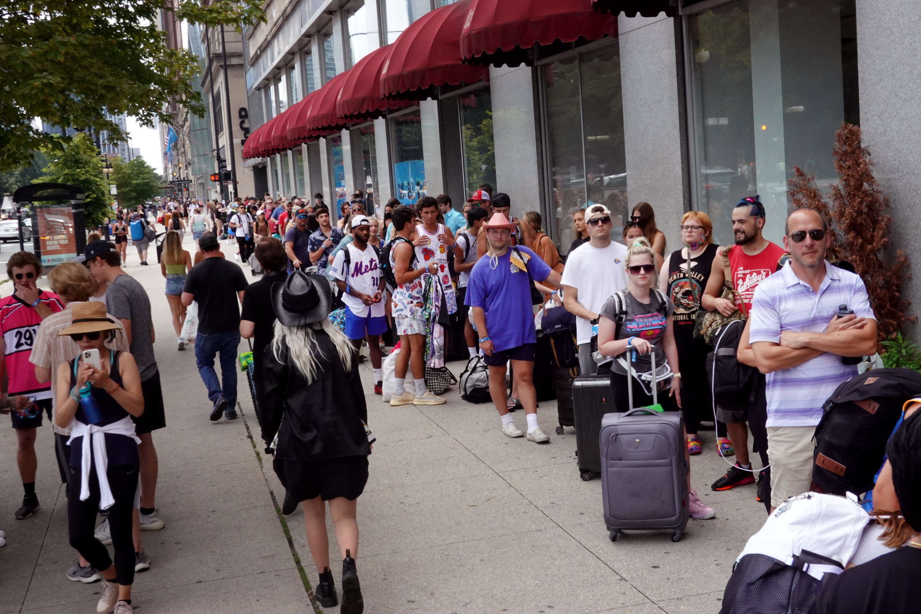 Lollapalooza music festival attendees form a line around a block in Chicago as they prepare to check in to their hotel.