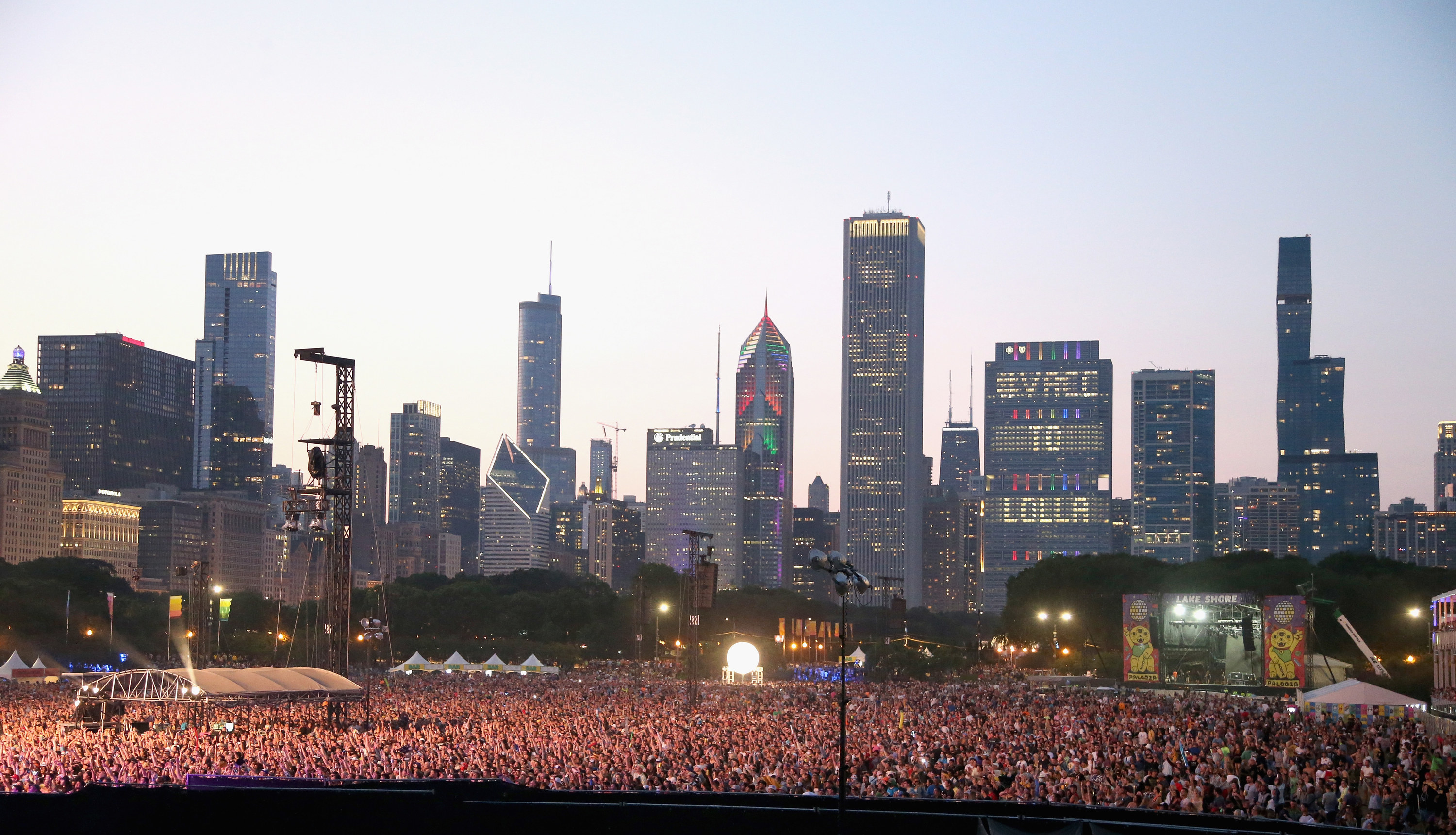 """The Chicago skyline lights up with the words """"Vacc to Lolla"""" behind a crowd of evening festival attendees at Lollapalooza music festival."""