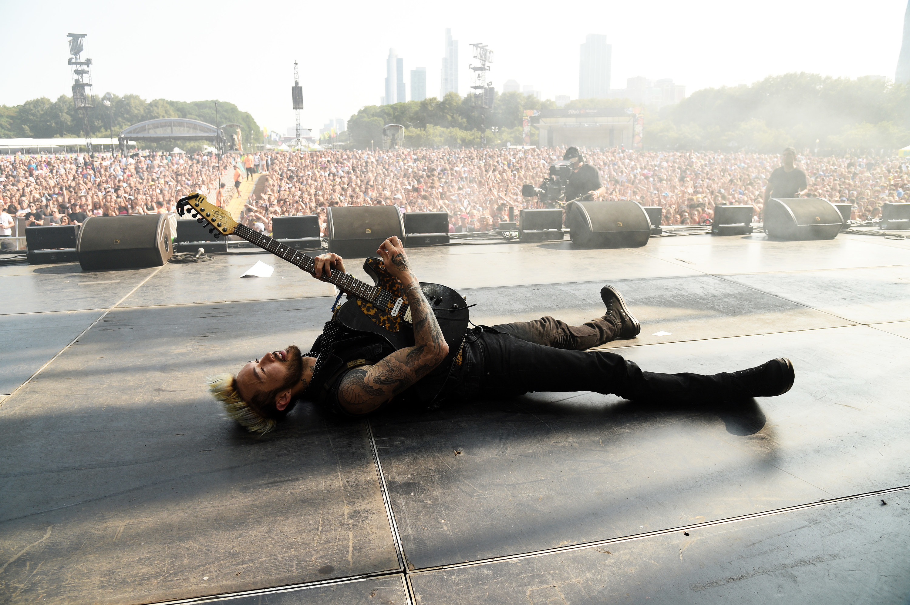 A musician is seen laying on stage holding a guitar as the crowd of thousands is seen in the background at Lollapalooza.