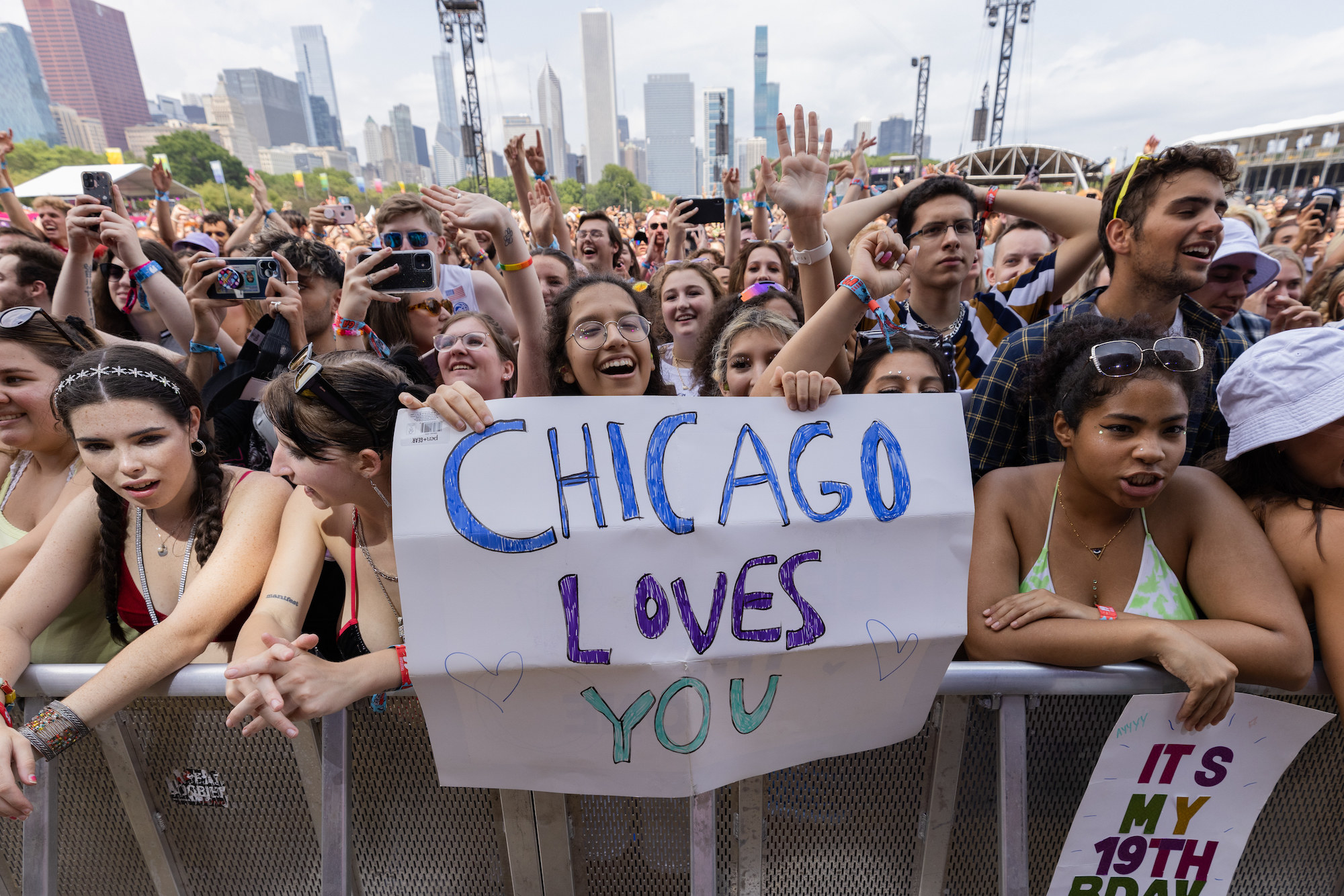 """Festival attendees hold a """"Chicago Loves You"""" sign as they await a performance at Lollapalooza."""