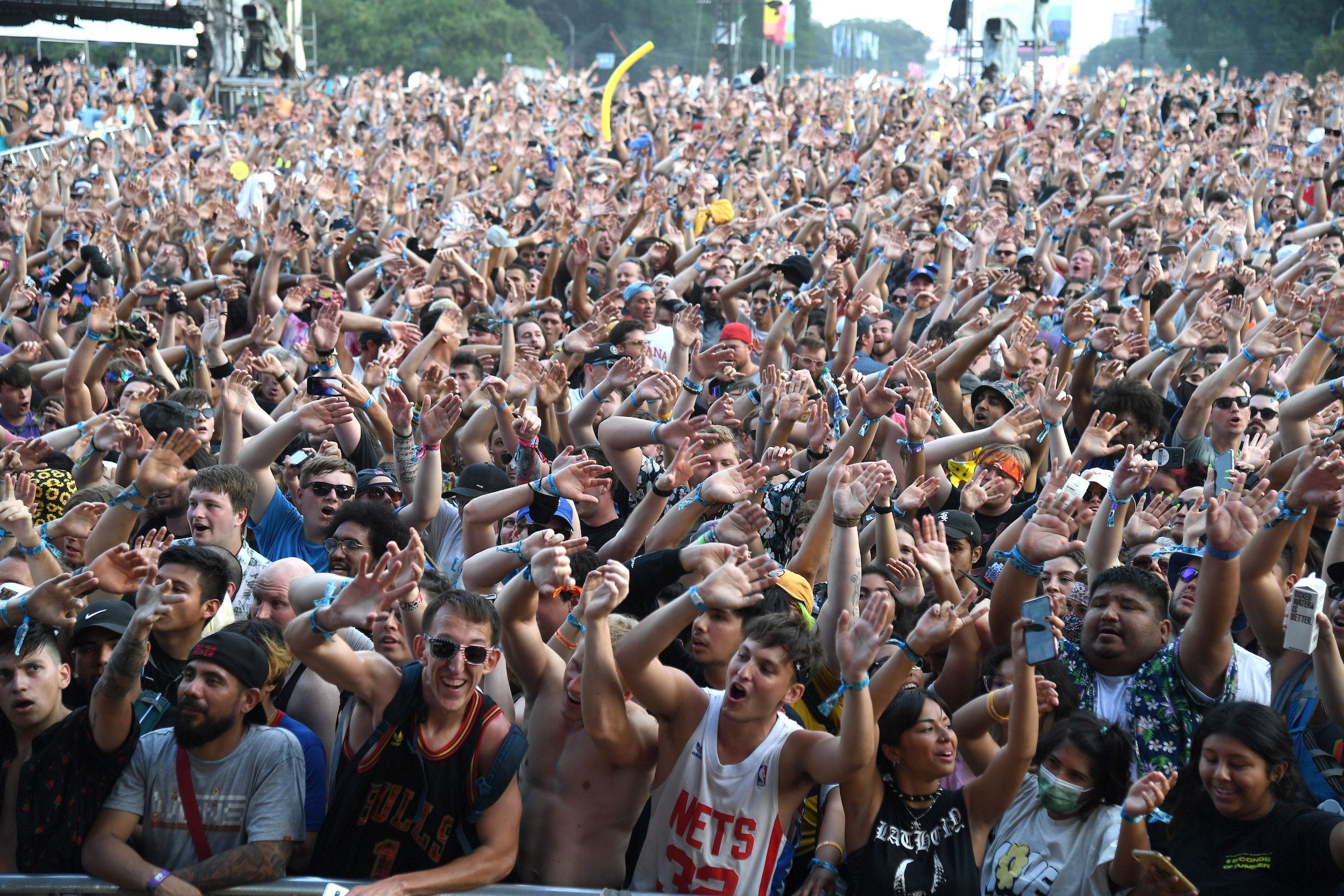 Hundreds of fans raise hands in the air and sing during an afternoon at Lollapalooza music festival.
