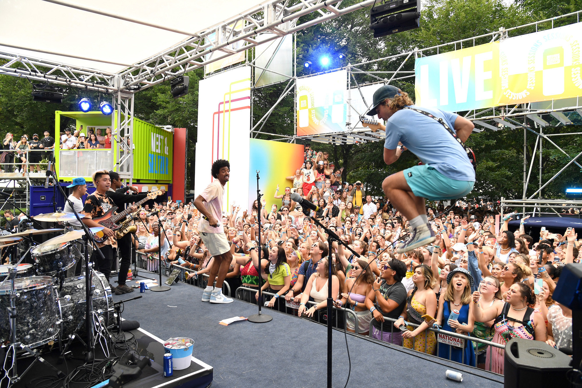 A musician is seen jumping high in the air with a guitar as an audience takes in a performance at Lollapalooza.