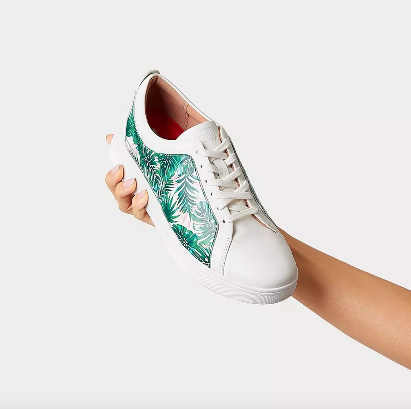 the jungle print leather sneakers being held by a reviewer