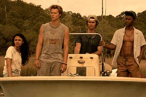 Kiara, JJ, John B, and Pope stand on a small boat as it goes through a swamp