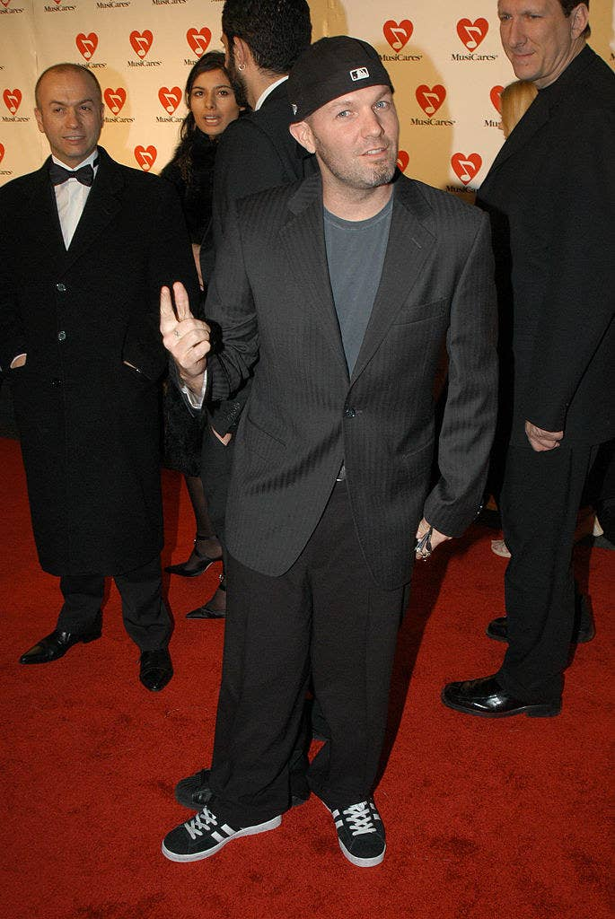 Fred wearing a suit with a tee-shirt, sneakers, and a baseball cap worn backwards on a red carpet