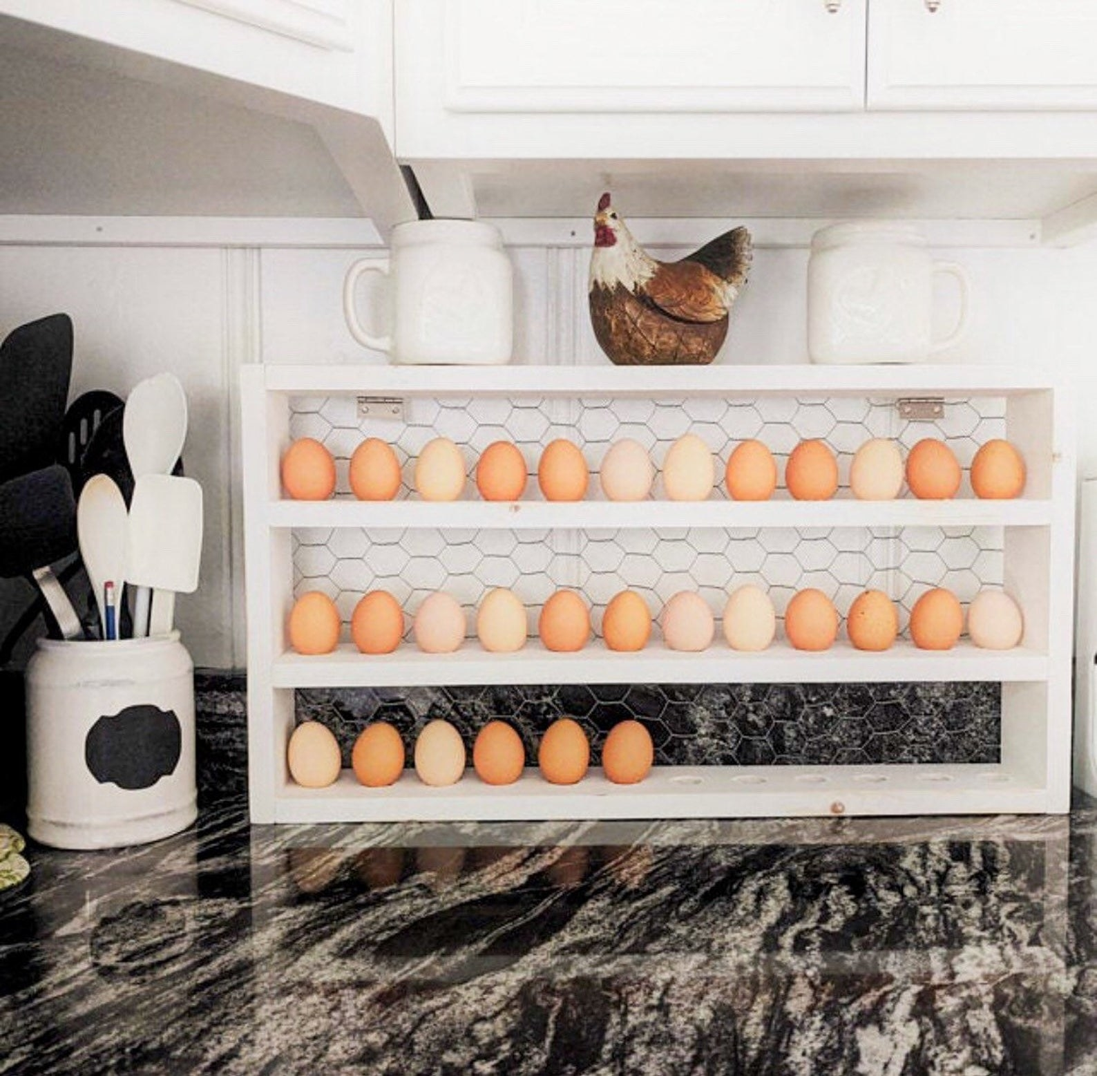 The white egg rack with eggs in it sitting on a counter