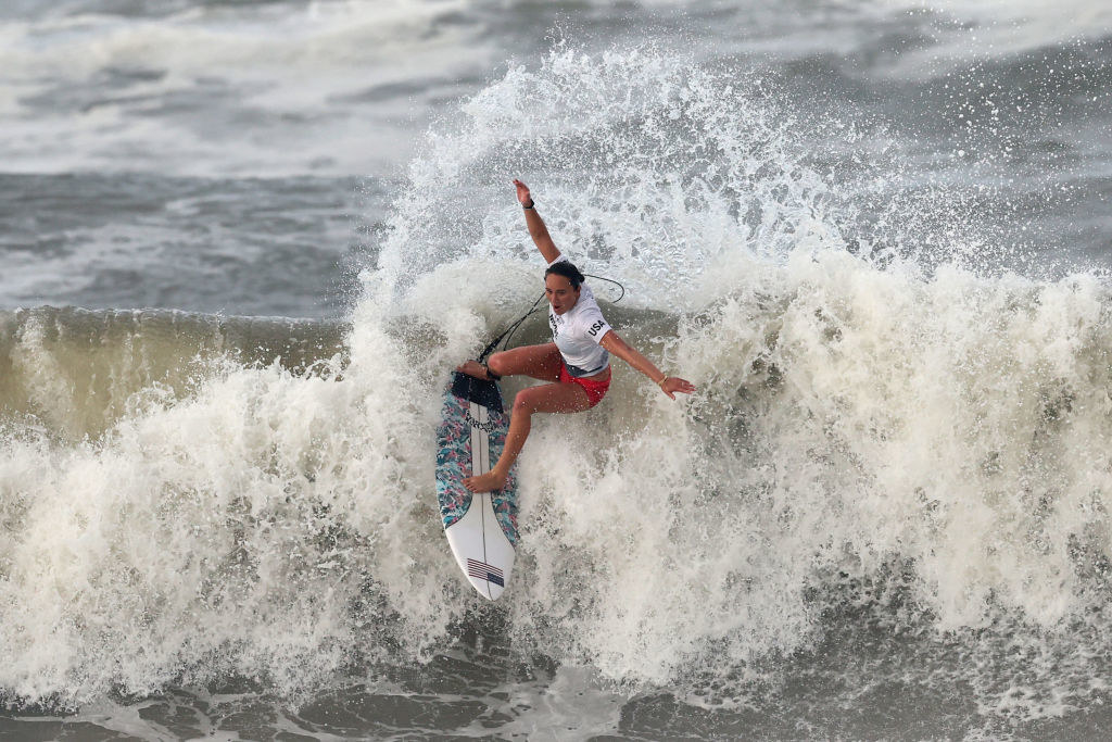 Moore surfing a big splashing wave with her arms spread open during her Olympics competition