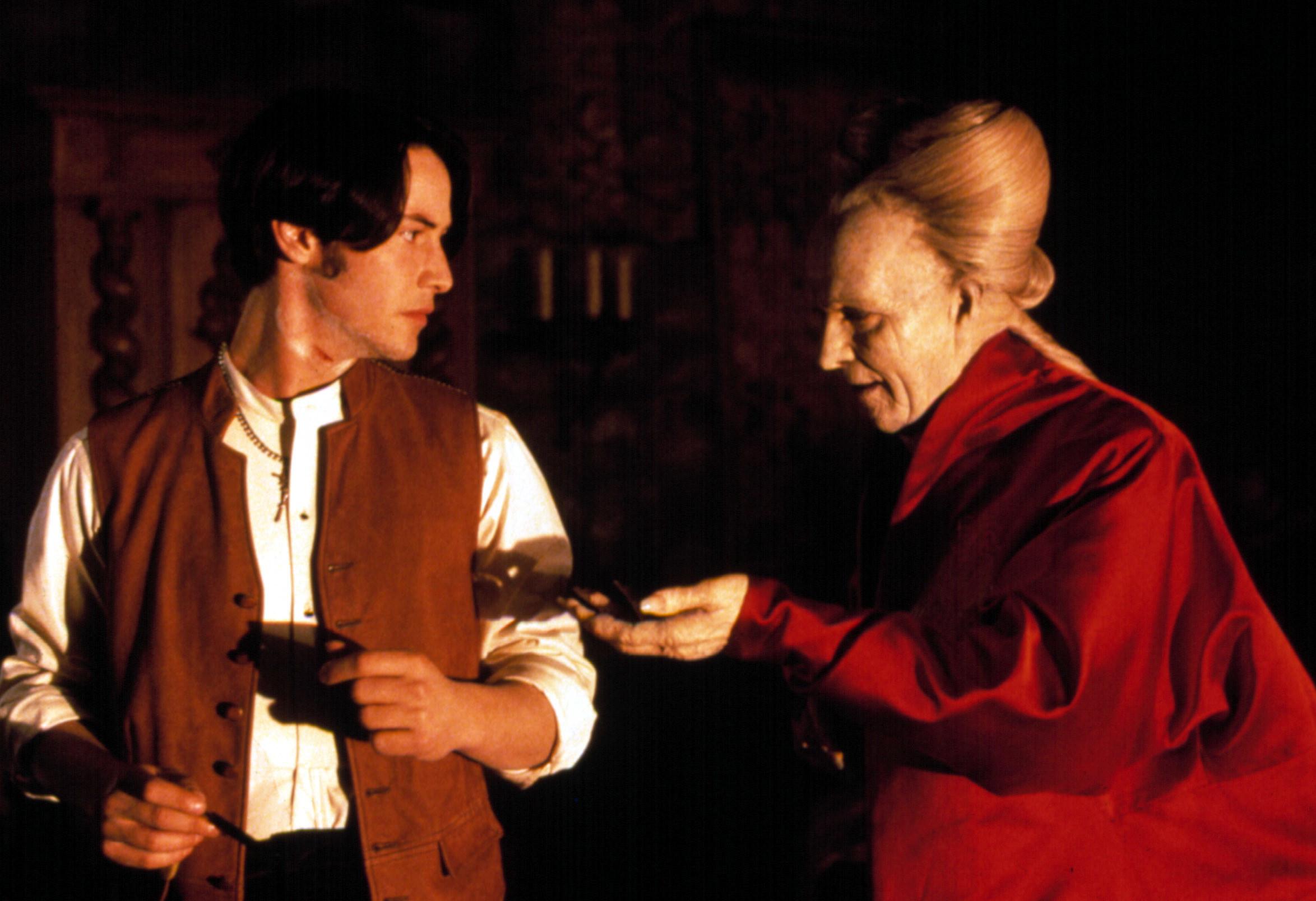 Keanu Reeves being offered something by Gary Oldman