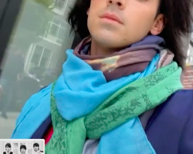 Joe is wearing several dark and light colored scarves with various prints