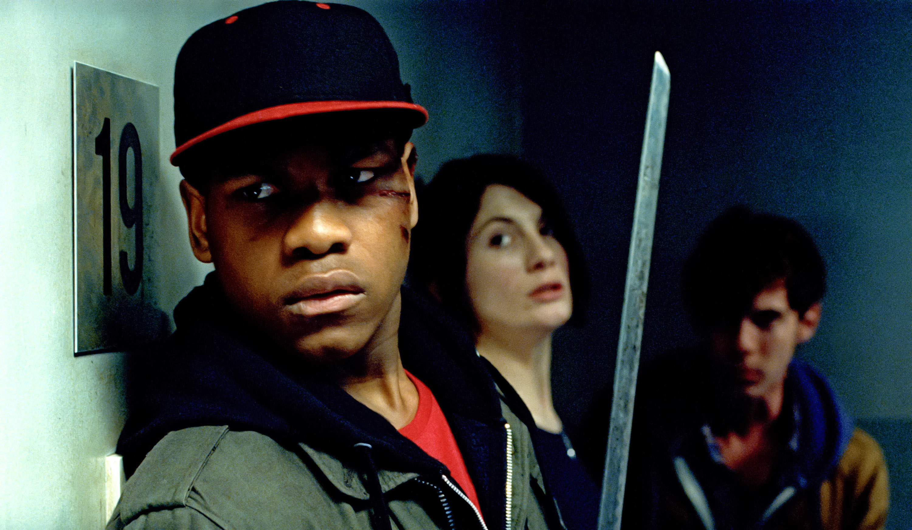 John Boyega holding a sword while Jodie Whittaker and Luke Treadaway look concerned.