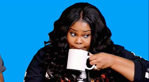 Amber Riley drinking from a mug and looking perplexed