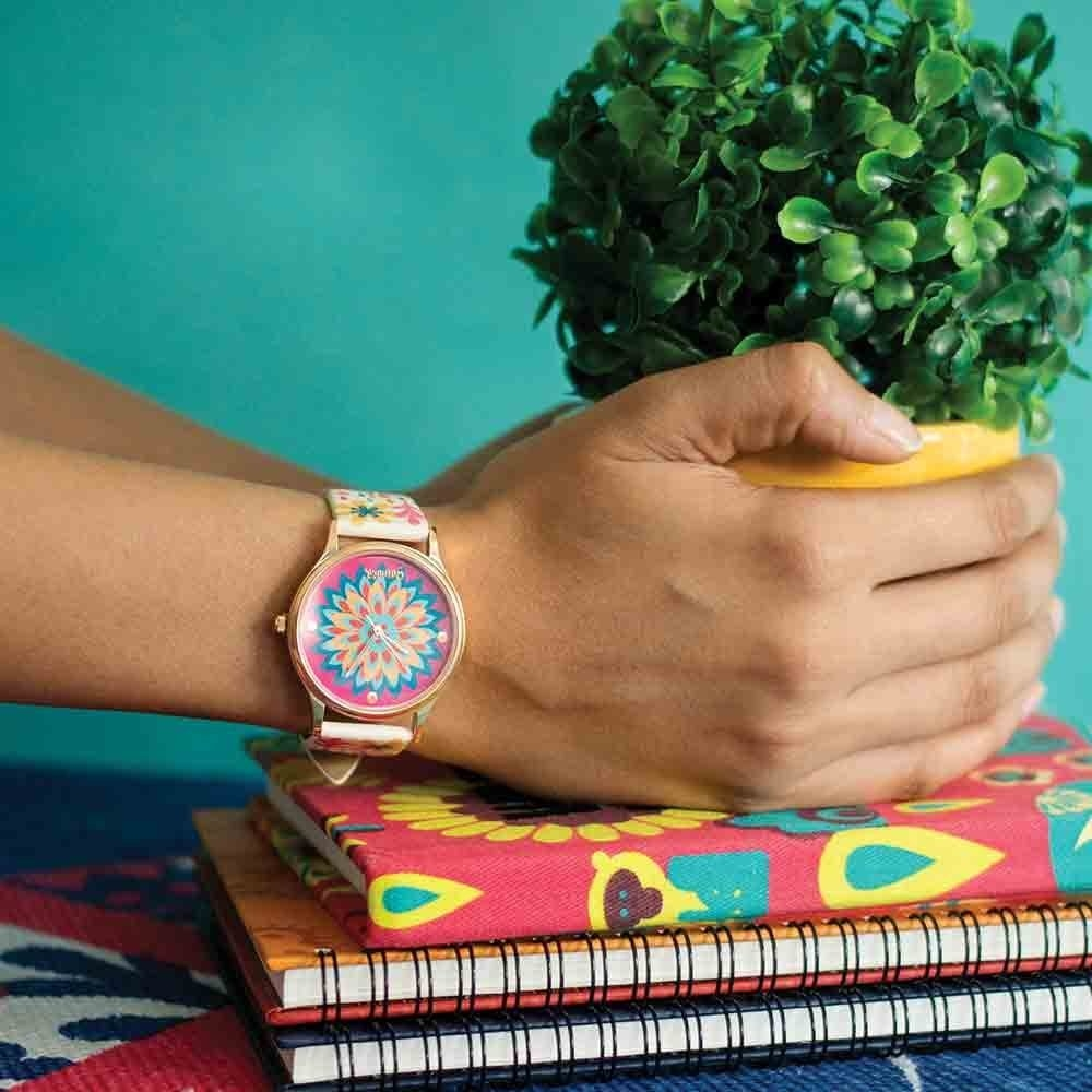 A person wearing a floral watch. They're holding a plant, which is kept on a pile of notebooks.