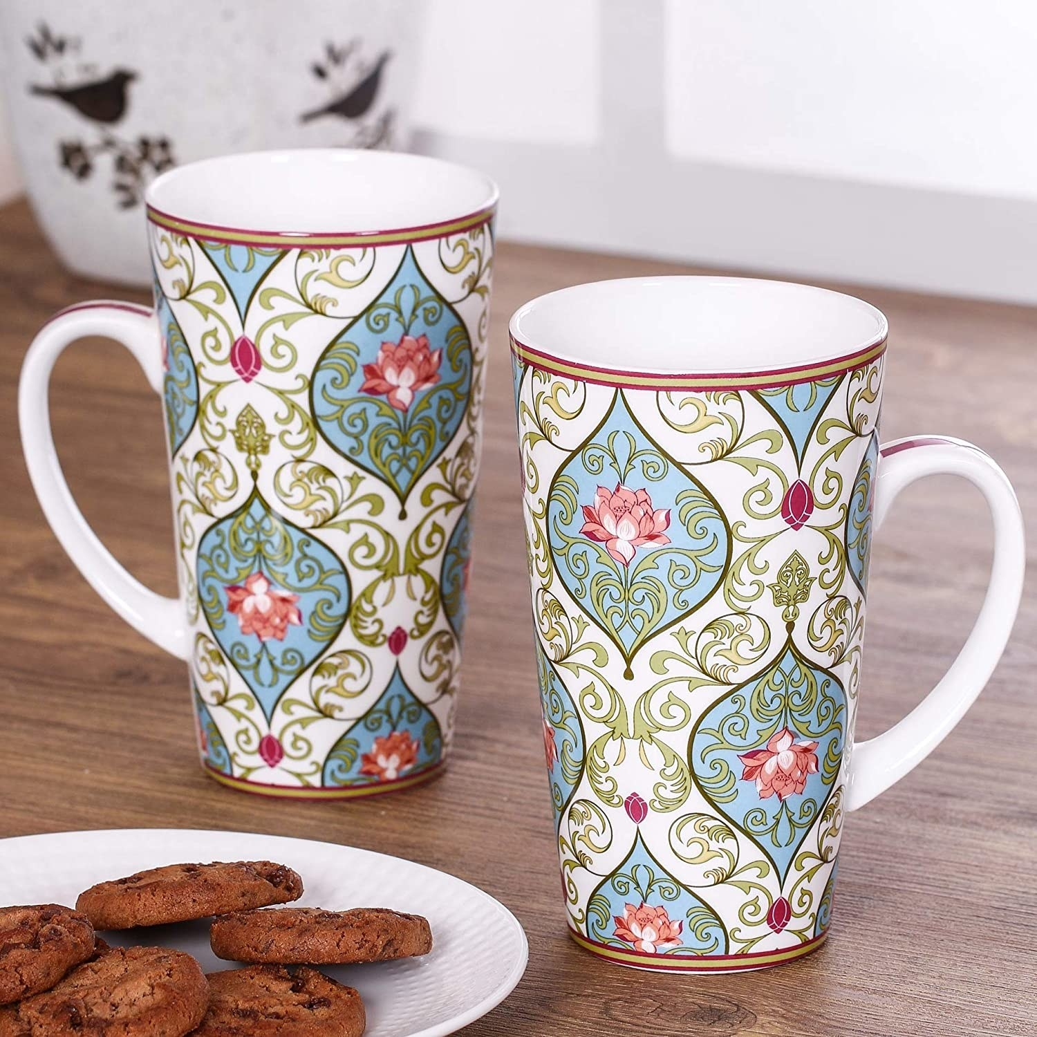 Two floral mugs next to a plate of cookies