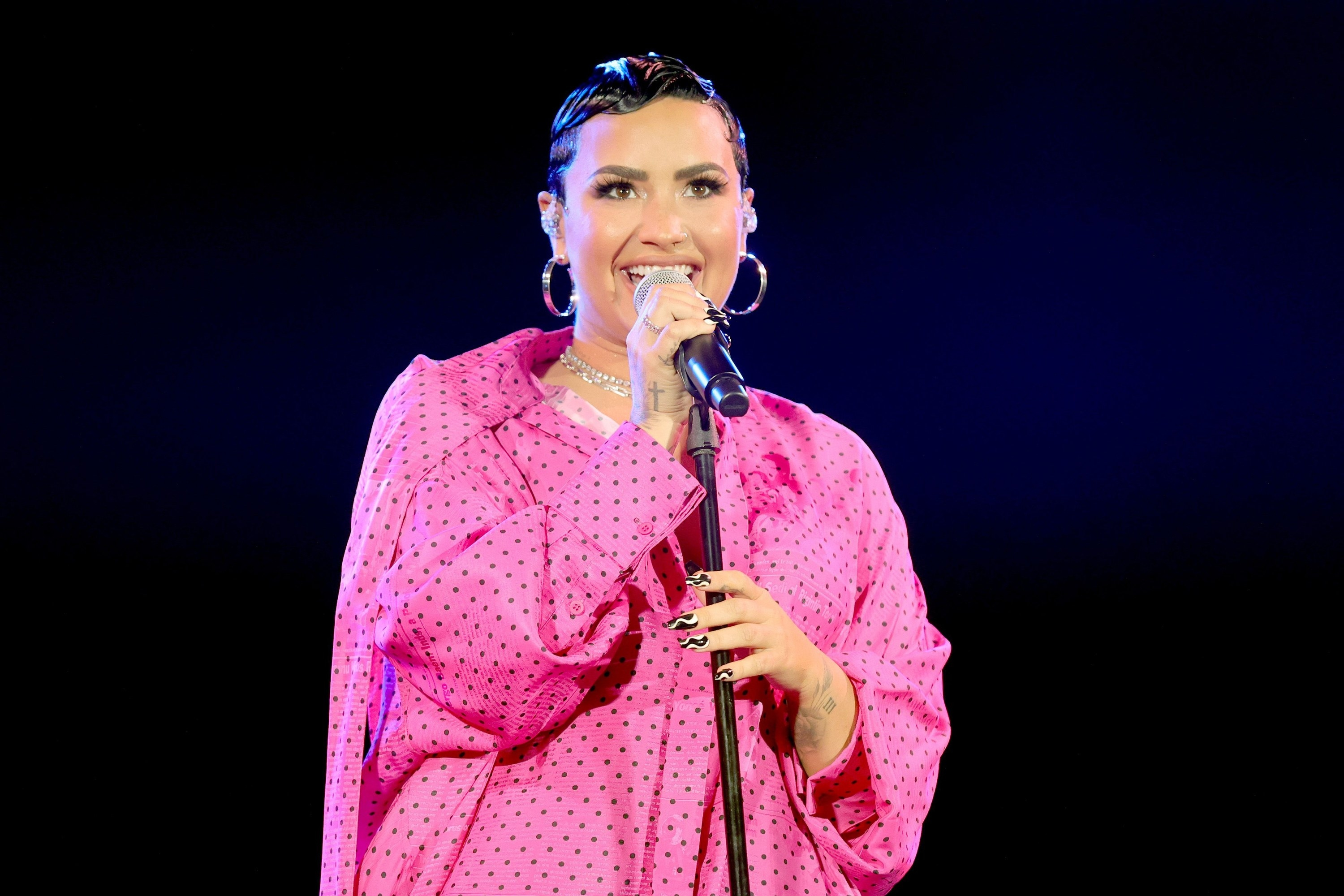 Demi smiles on stage while wearing a pink polka dot oversize shirt