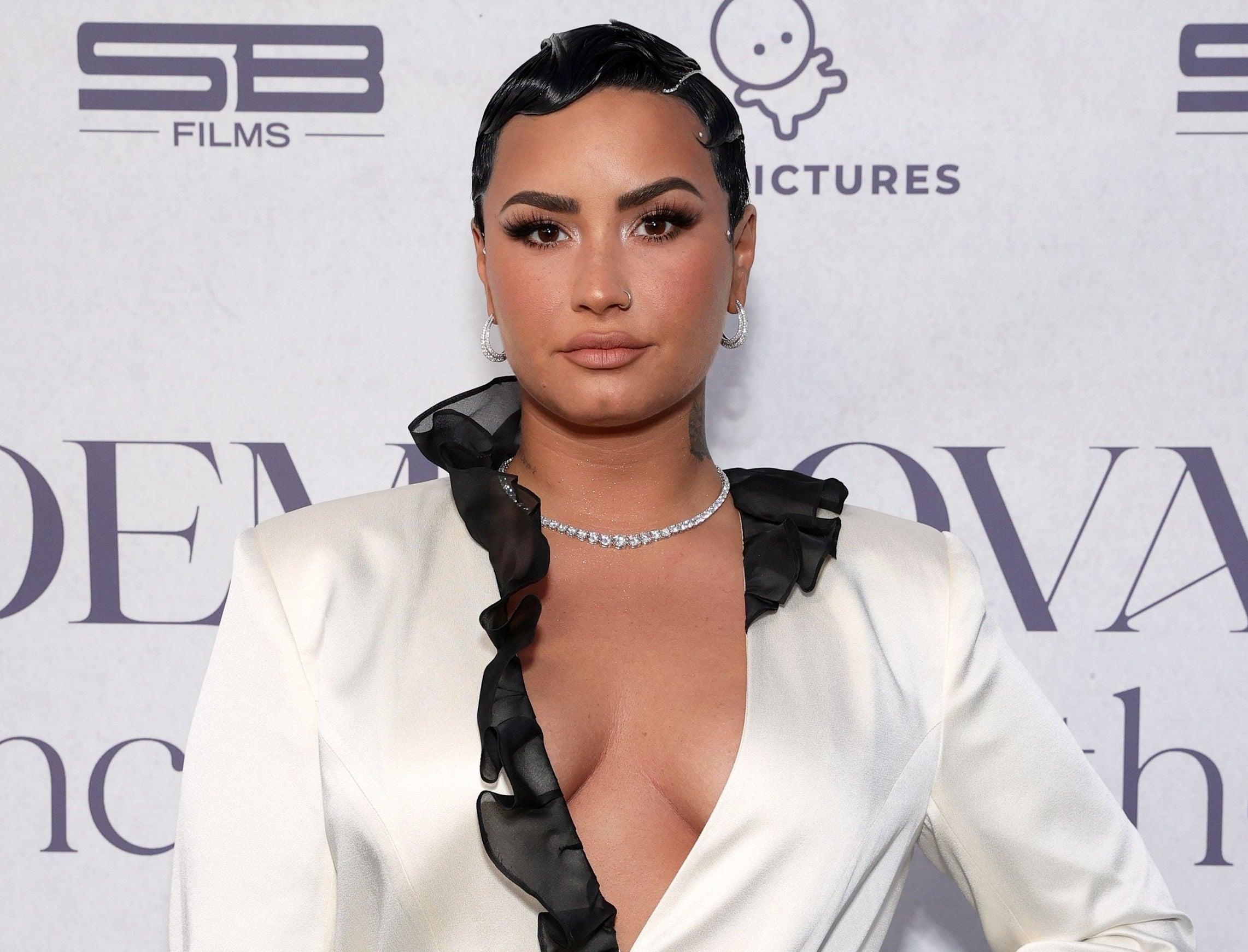 Demi wears a white blazer with black ruffle trim