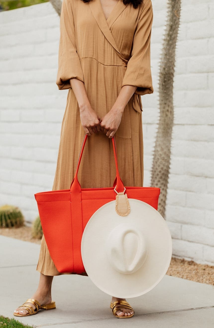 A hat hanging from the raffia clip attached to a tote handle