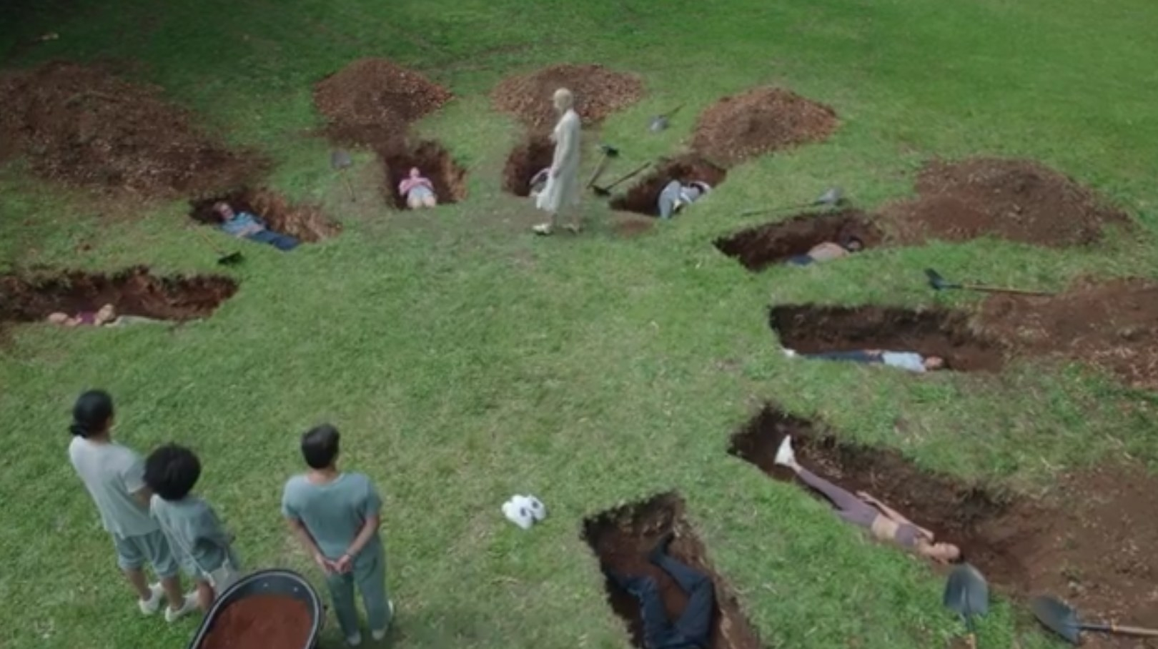 The guests lay in open graves set out in a circle while Tranquillum staff stand above them
