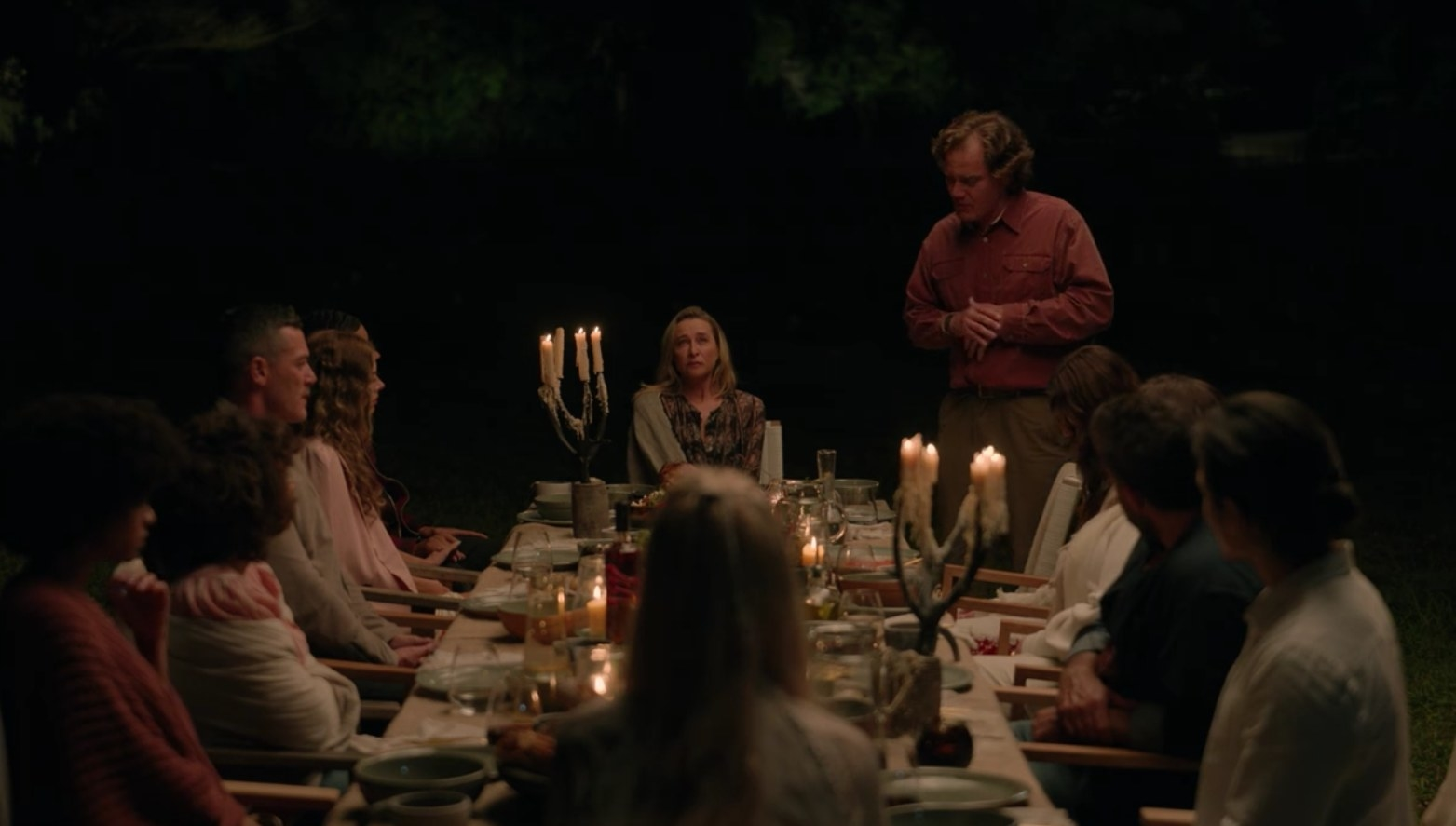 The guests sit around a dinner table outdoors at nighttime, Napoleon is standing to speak to them all