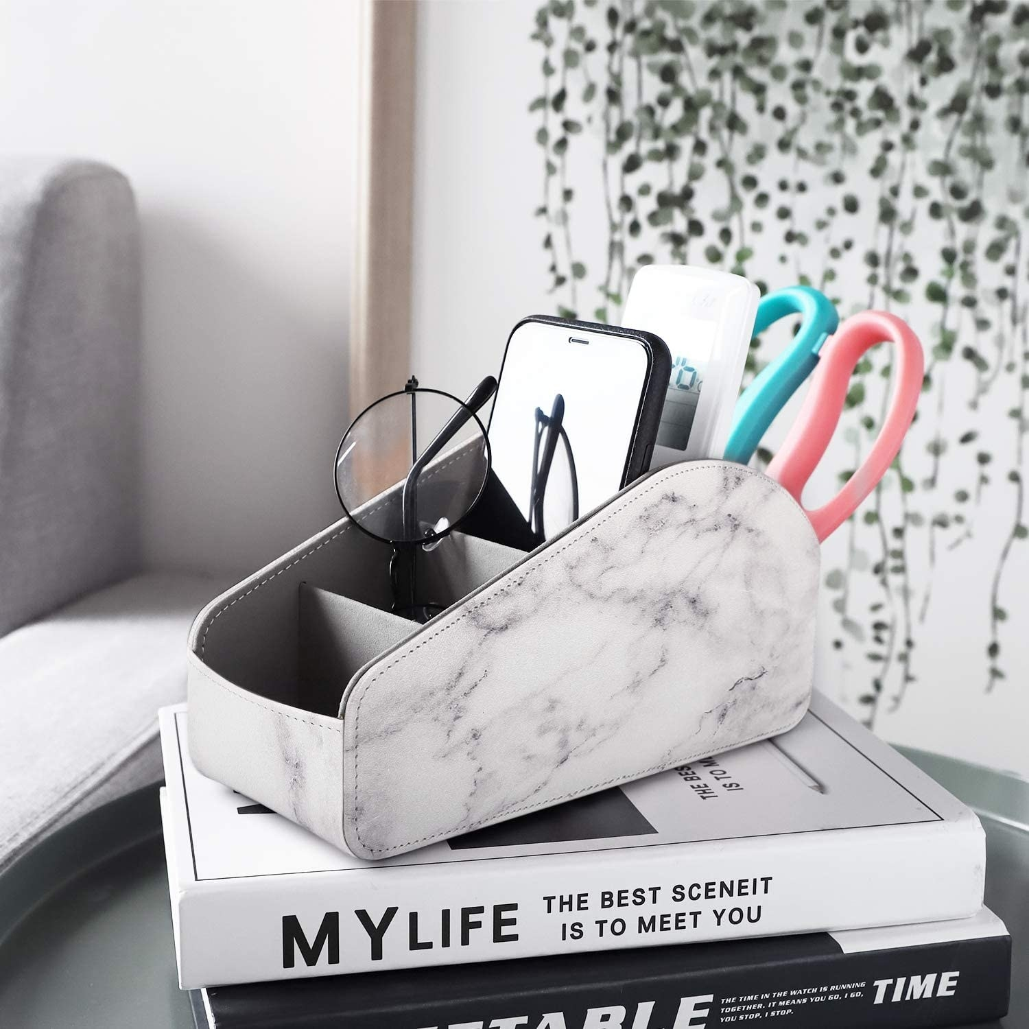 A fabric remote control organizer sitting on a stack of books There are a pair of glasses, a phone, a remote, and a pair of scissors in a different compartment