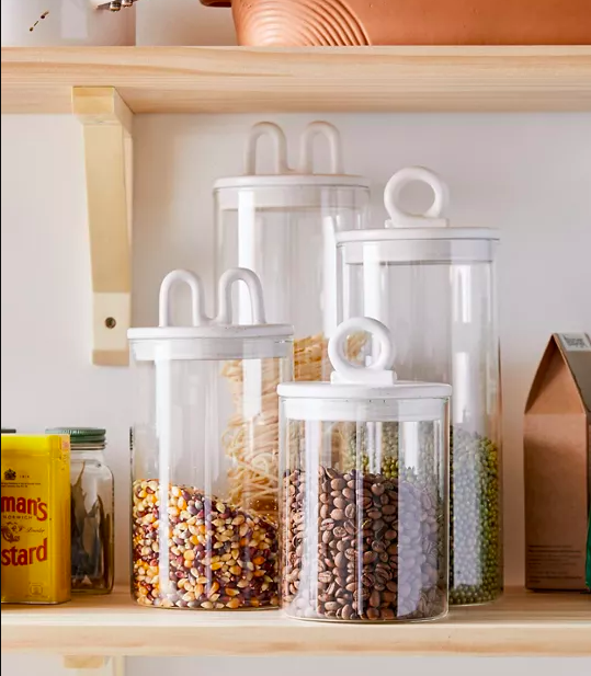 Four storage containers of different sizes filled with dried foods