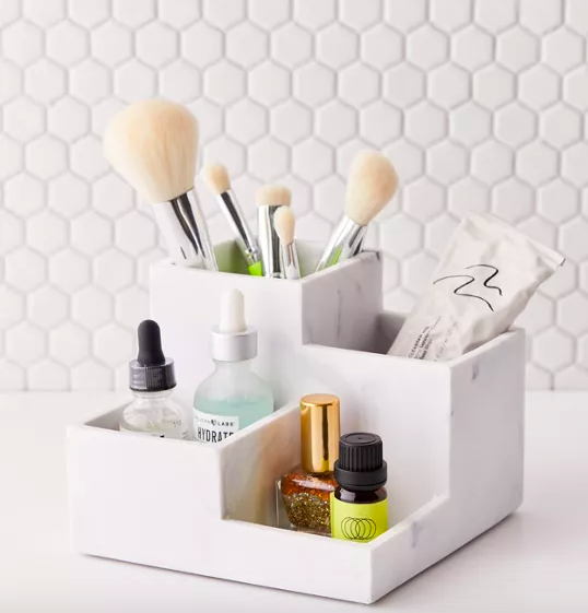 A marble makeup organizer with brushes and beauty products in it
