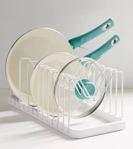 Two pans and a lid on an organized wire shelf