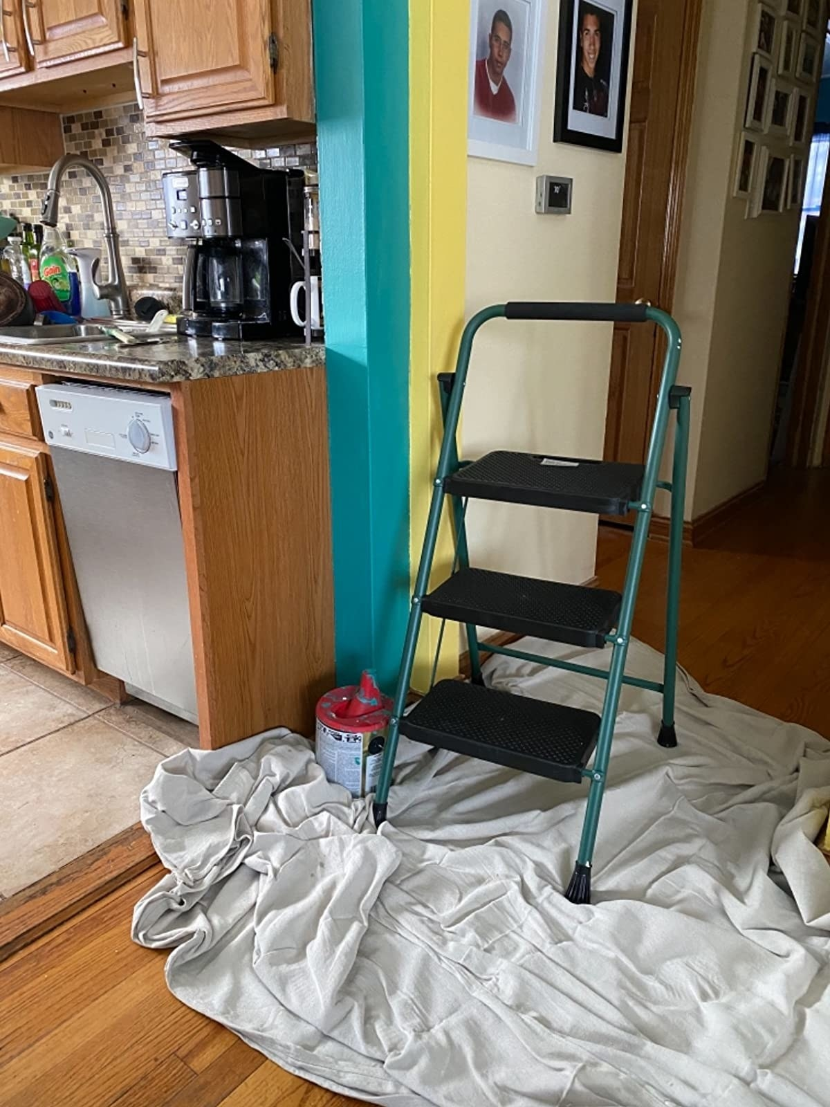 reviewer image of the drop cloth on the floor by a wall being painted