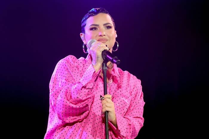 Demi performing onstage in a polka dot shirt