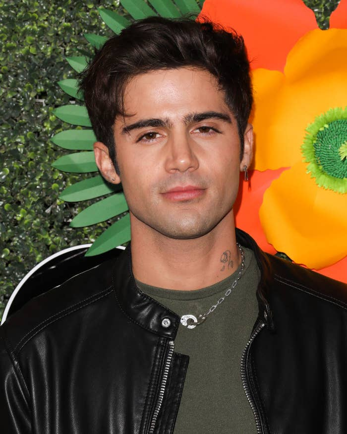 Max Ehrich posing on a red carpet in a T-shirt and leather jacket