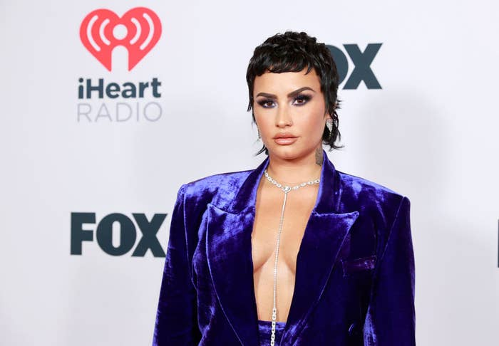 Demi posing on a red carpet in a velvet suit with no shirt underneath and a long diamond necklace