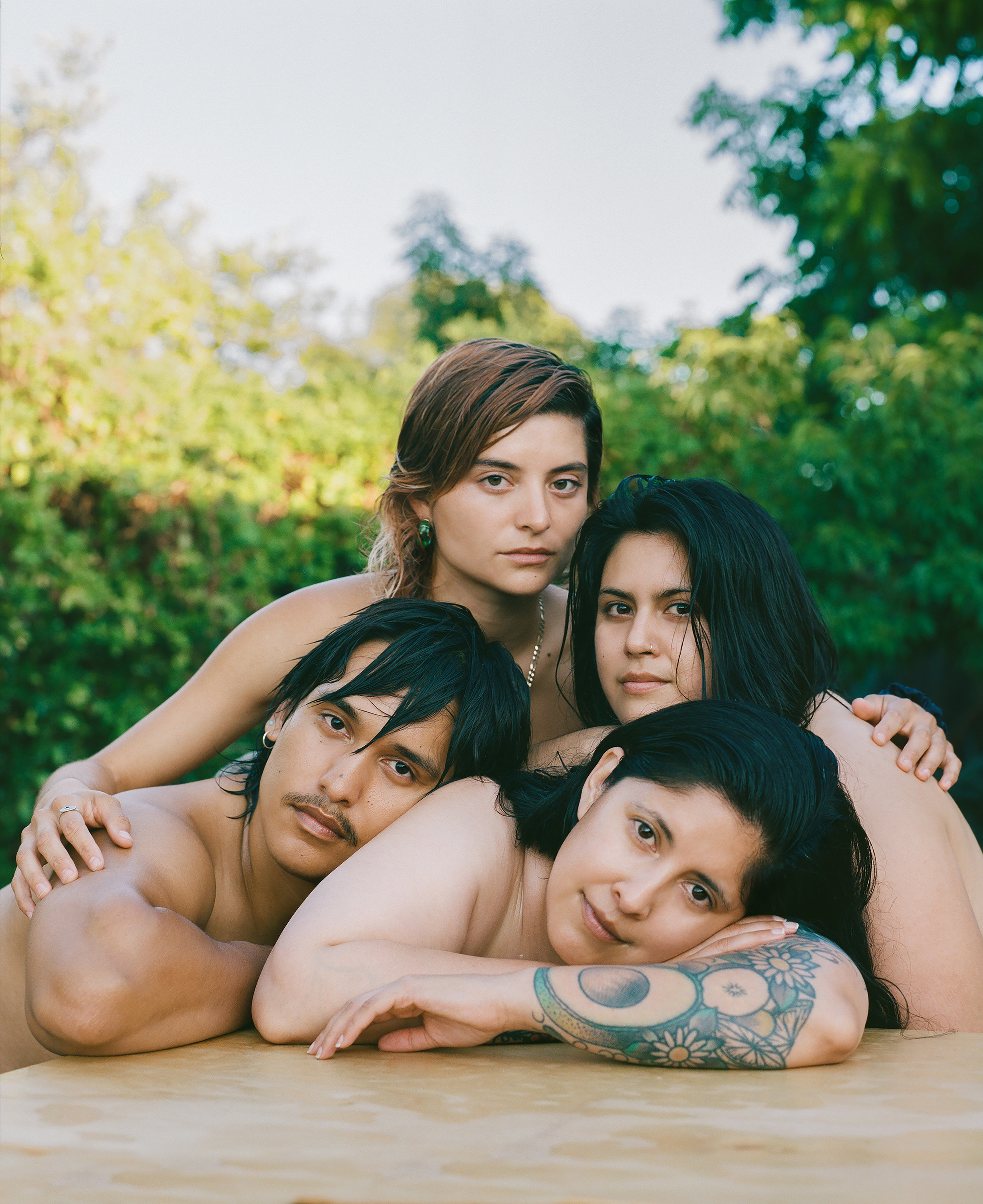 Four people, apparently naked, leaning on one another with their torsos on a plywood table
