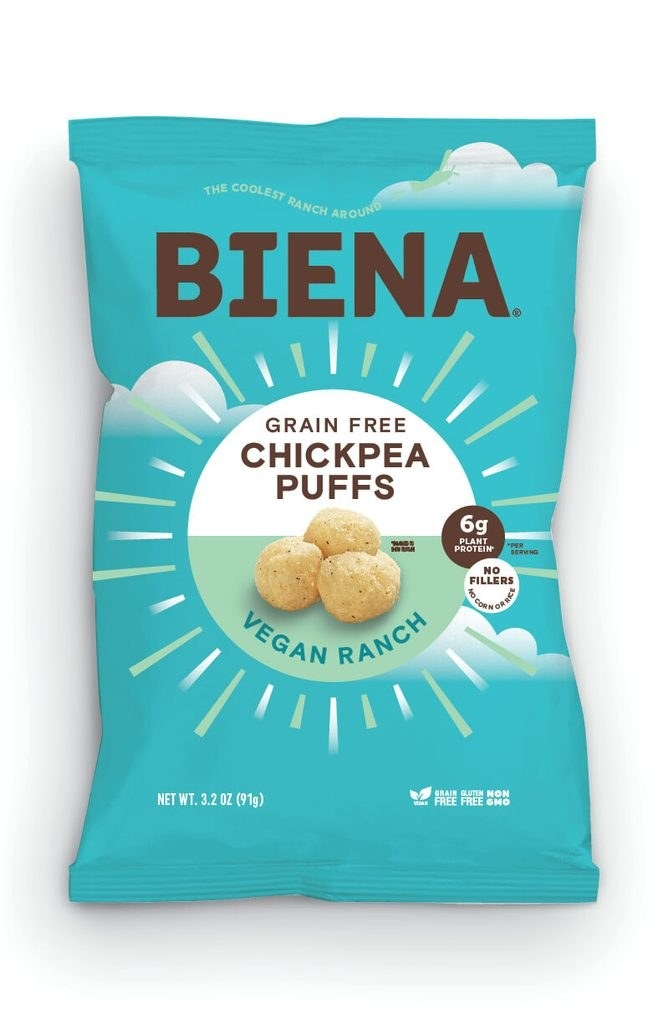 """A turquoise bag that says """"grain free chickpea puffs"""" on it"""