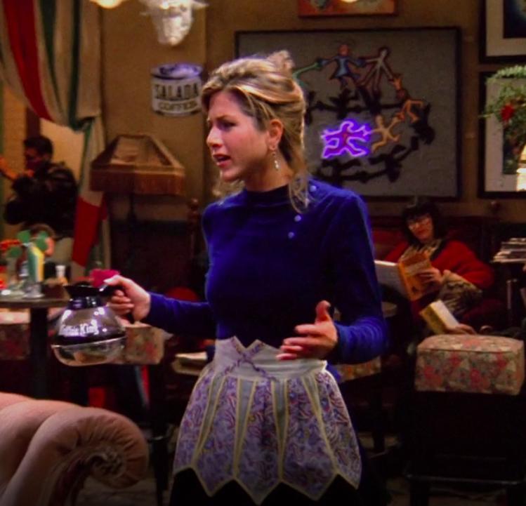Rachel wearing a blue velvet shirt and a pretty apron over a black skirt