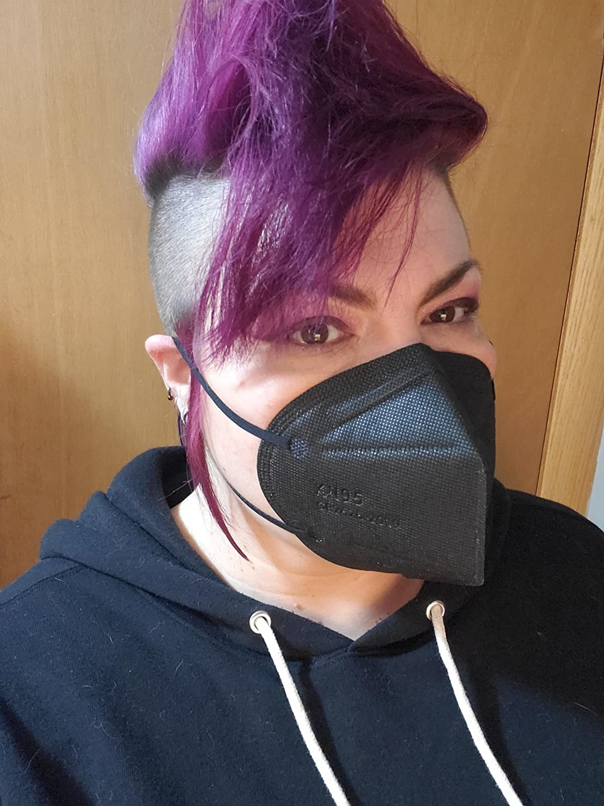 reviewer with a purple mohawk wearing the black KN95 face mask