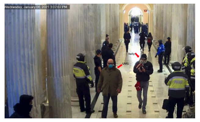 A number of people, including several wearing police uniforms, stand and walk along a hallway