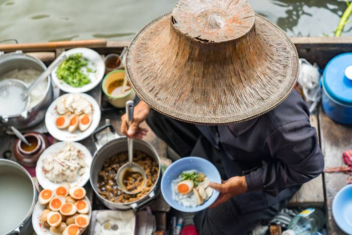 A woman serving food from a floating market.