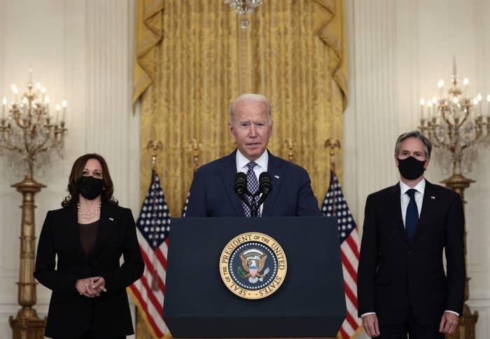 Joe Biden, Kamala Harris, and Antony Blinken stand by a lectern in the White House